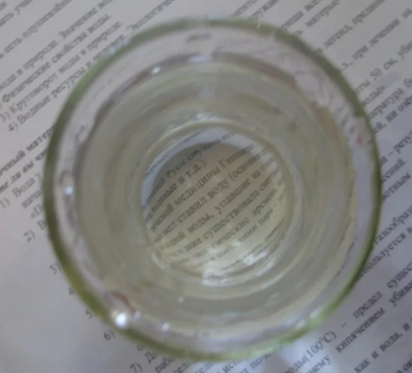 Определение чистоты воды при помощи стакана и бумаги с текстом
